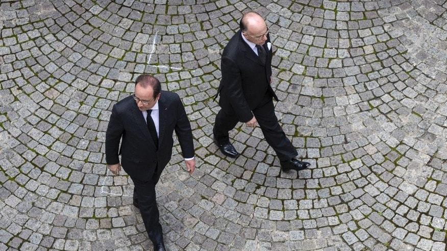 FILE - In this Wednesday, June 15, 2016 file picture, French President Francois Hollande, left, and Interior Minister Bernard Cazeneuve arrive for an homage ceremony for the two police officials killed by an Islamic State extremist, at the French Interior Ministry in Paris, France. French Prime Minister Manuel Valls has stepped down to focus on running for president in next year's election and has been replaced by Interior Minister Bernard Cazeneuve. (AP Photo/Kamil Zihnioglu, File)