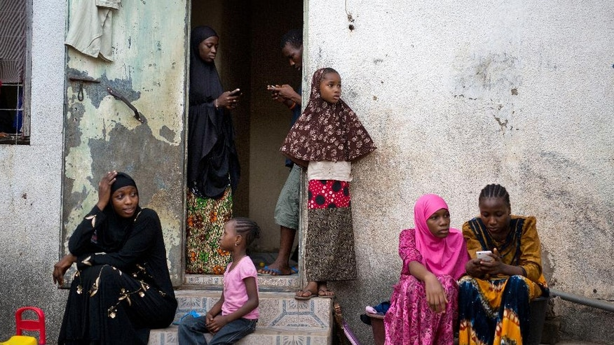 In this photograph taken Saturday, Dec. 3, 2016, Fatoumata Sawaneh, left, sits with relatives in the family's Kanifing, Gambia's home. Sawaneh has not heard from her father since, and fears for his life. Sawaneh tries desperately to hold back tears while talking about her father, Imam Ousman Sawaneh of Kanifing South, who was among three imams arrested in October 2015. She has not heard from him since, and like so many others in Gambia, fears for their loves ones' life.Though the sudden disappearances are often unexplained, it is a familiar tale for so many under President Yahya Jammeh's 22-year rule, which has created a climate of fear and mistrust. (AP Photo/Jerome Delay)