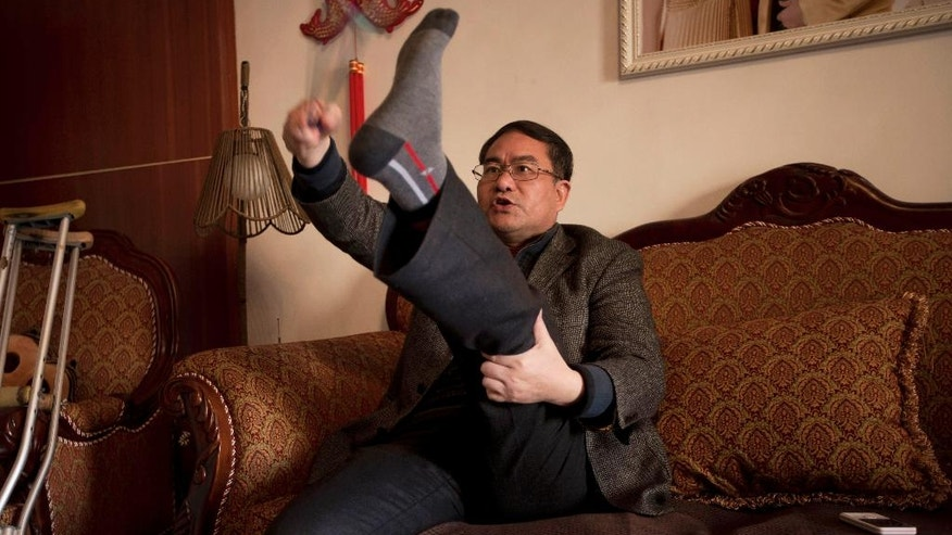 FILE - In this Monday, Jan. 20, 2014, file photo, Zhou Wangyan, head of the Liling city land resources bureau, demonstrates how he was tortured by Communist Party anti-graft investigators who struck at the soles of his feet with wires, during an interview in his home in Liling in central China's Hunan province. Zhou said he was detained by anti-corruption investigators for 184 days, during which he he was whipped, forced to eat excrement, beaten and physically tortured, his legs pushed apart until his thigh bone snapped in several places. (AP Photo/Andy Wong, File)