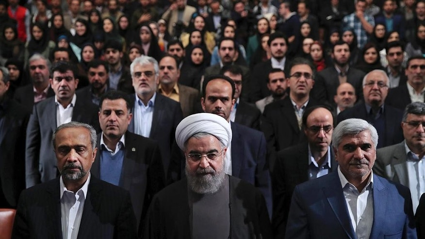 "In this photo released by official website of the office of the Iranian Presidency, President Hassan Rouhani, center, Science Minister Mohammad Farhadi, right, and head of the President's office Mohammad Nahavandian, left, listen to the national anthem at the start of a ceremony marking Student Day at Tehran University in Tehran, Iran, Tuesday, Dec. 6, 2016. Rouhani said Tuesday his country will not allow incoming U.S. President Donald Trump to ""tear up"" Tehran's landmark nuclear deal with world powers. His remarks underscore Iranian leaders' attempts to calm concerns over the future of the deal in the wake of Trump's election. (Iranian Presidency Office via AP)"