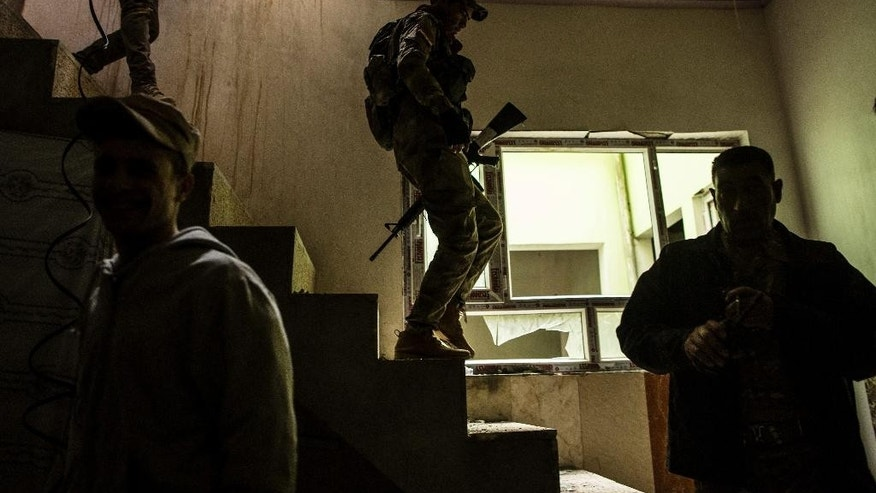 Iraqi soldiers are seen within a building at the frontline in the Al-Intisar district in Mosul, Iraq, Monday, Dec. 5, 2016. Mosul, Iraq's second-largest city, is the last major Islamic State extremist urban bastion in the country. Iraqi troops have advanced cautiously to avoid civilian casualties. (AP Photo/Manu Brabo)