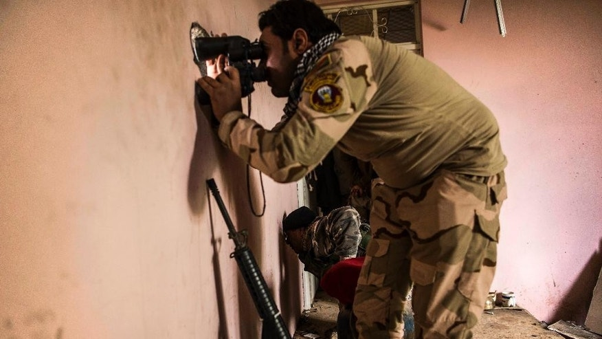 Iraqi soldiers from the 9th division looks through a sniper hole at the Al-Intisar district in Mosul, Iraq, Monday, Dec. 5, 2016. Mosul, Iraq's second-largest city, is the last major Islamic State extremist urban bastion in the country. Iraqi troops have advanced cautiously to avoid civilian casualties. (AP Photo/Manu Brabo)