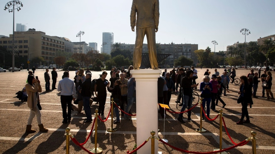 People watch a statue of Israeli Prime Minister Benjamin Netanyahu at the central square in Tel Aviv, Tuesday, Dec. 6.