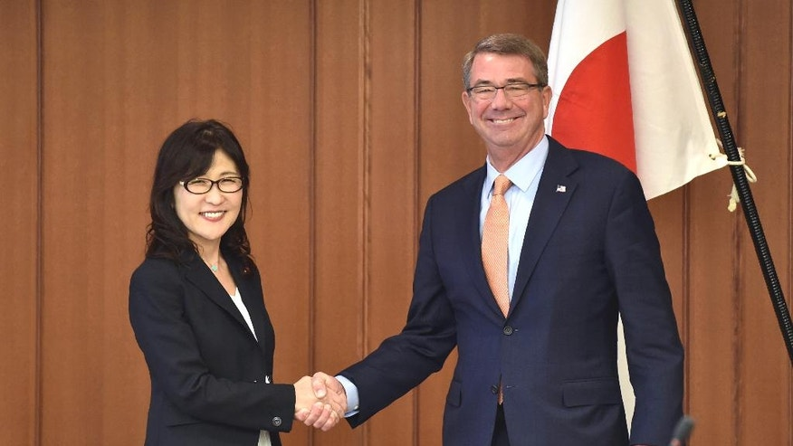 U.S. Secretary of Defense Ash Carter, right, and Japanese Defense Minister Tomomi Inada pose for a photo prior to their meeting at the Defense Ministry Tokyo, Wednesday, Dec. 7, 2016. The U.S. and Japan announced Tuesday that Washington will give back to the Japanese government nearly 10,000 acres of land on Okinawa that U.S. Marines use for jungle warfare training. (Kazuhiro Nogi/Pool Photo via AP)