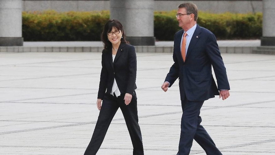 U.S. Secretary of Defense Ash Carter, right, and Japanese Defense Minister Tomomi Inada walk after inspecting an honor guard at the Defense Ministry Tokyo, Wednesday, Dec. 7, 2016. The U.S. and Japan announced Tuesday that Washington will give back to the Japanese government nearly 10,000 acres of land on Okinawa that U.S. Marines use for jungle warfare training. (AP Photo/Eugene Hoshiko)