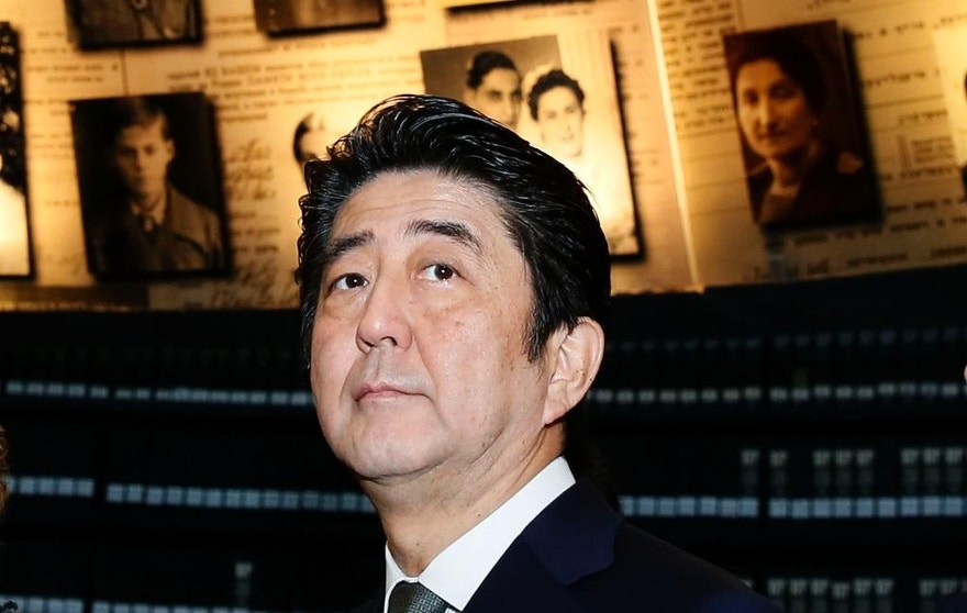 FILE - In this Monday, Jan. 19, 2015, file photo, Japanese Prime Minister Shinzo Abe looks at photos of Jewish Holocaust victims at the Hall of Names, during his visit to the Yad Vashem Holocaust Memorial museum, in Jerusalem. The release of an online video Tuesday purporting to show an Islamic State figure demanding $200 million in ransom for two Japanese hostages ambushed Prime Minister Shinzo Abe as he was wrapping up a six-day tour of the Middle East.  (AP Photo/Gali Tibbon, Pool)