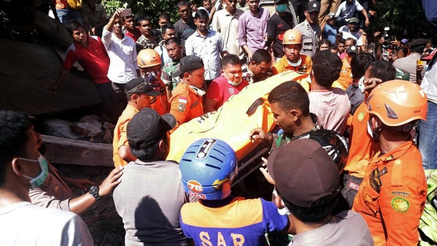 Rescuers carry a body bag containing the body of a victim recovered from under the rubble of a building that collapsed after an earthquake in Pidie Jaya, Aceh province, Indonesia, Wednesday, Dec. 7, 2016. A strong undersea earthquake rocked Indonesia's Aceh province early on Wednesday, killing a number of people and causing dozens of buildings to collapse. (AP Photo/Heri Juanda)