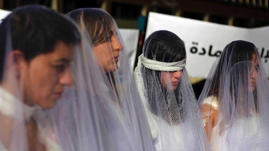 A dozen Lebanese women, dressed as brides in white wedding dresses stained with fake blood and bandaging their eyes, knees and hands stand in front of the government building in downtown Beirut, Lebanon, Tuesday, Dec. 6, 2016. The activists are protesting a Lebanese law that allows a rapist to get away with his crime if he marries the survivor. The law, in place since the late 1940s, is currently reviewed in Lebanese parliament. Campaigners against the law are calling on lawmakers to repeal the law during their meeting Wednesday. (AP Photo/Bilal Hussein)
