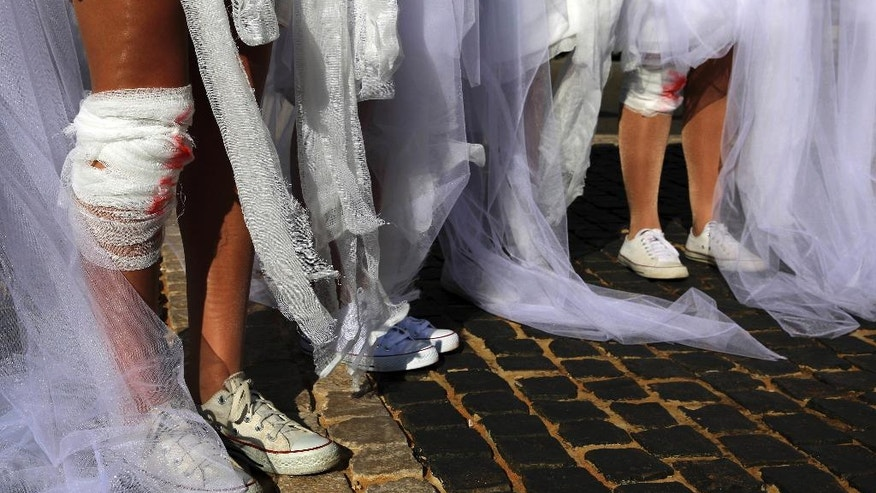 Women activists put on fake bandage and blood stains around their legs and body, while they dressed as brides in white wedding dresses during a protest in front of the government building in downtown Beirut, Lebanon, Tuesday, Dec. 6, 2016. The activists are protesting a Lebanese law that allows a rapist to get away with his crime if he marries the survivor. The law, in place since the late 1940s, is currently reviewed in Lebanese parliament. Campaigners against the law are calling on lawmakers to repeal the law during their meeting Wednesday. (AP Photo/Bilal Hussein)