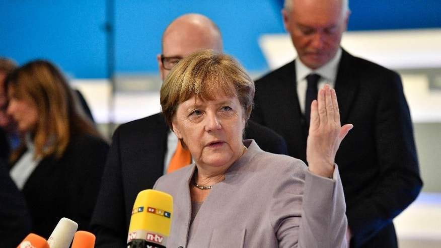 German Chancellor Angela Merkel talks to the media prior to the general party conference of the Christian Democratic Union, CDU, in Essen, Germany, Monday, Dec. 5, 2016. Merkel wants secure the backing of her conservative party to head up the party's campaign for next September's election. (AP Photo/Martin Meissner)
