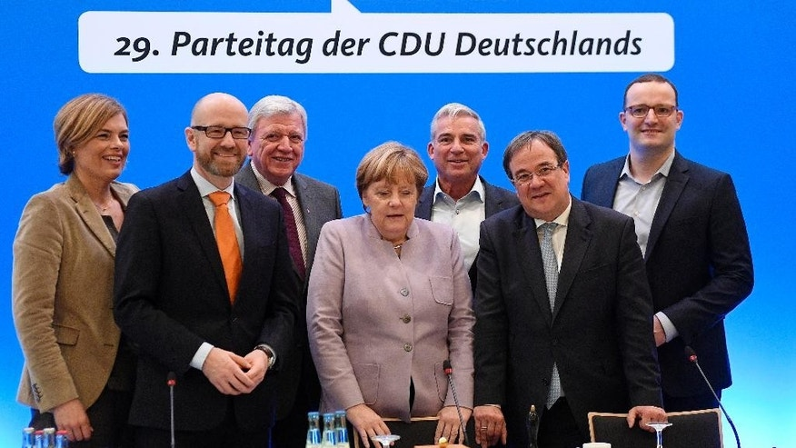 German Chancellor Angela Merkel, center, is standing with the board members at a meeting prior to the general party conference of the Christian Democratic Union, CDU, in Essen, Germany, Monday, Dec. 5, 2016. Merkel wants to secure the backing of her conservative party to head up the party's campaign for next September's election. (AP Photo/Martin Meissner)