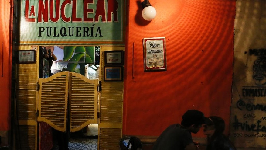 In this Dec. 2, 2016 photo, a couple sit outside La Nuclear pulqueria in Mexico City. Mexicans have been brewing pulque from the juice of cactus-like maguey plants for centuries, but the viscous, beer-like beverage fell out of favor starting in the 1970s as pulque got a reputation as a poor man's drink. (AP Photo/Marco Ugarte)