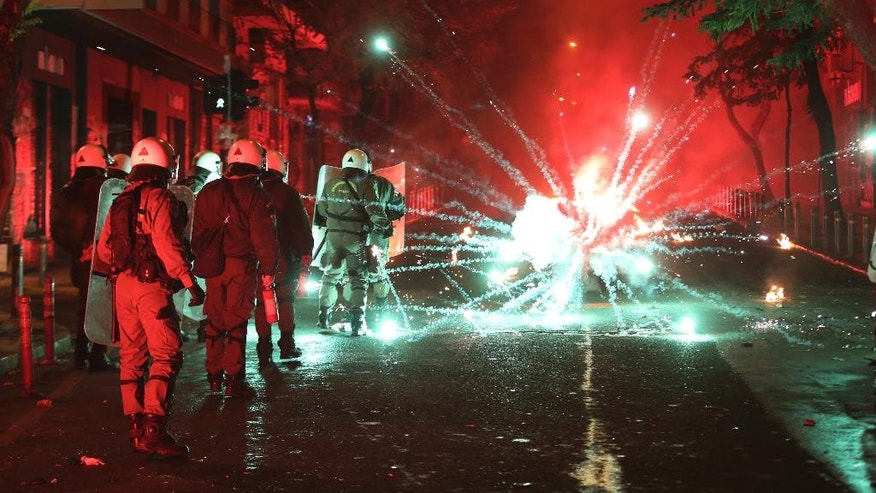 Protesters throw fireworks and flares at riot police during clashes in Athens, on Tuesday, Dec. 6, 2016. Riots have broken out in central Athens, with dozens of youths throwing petrol bombs at police after a peaceful march to commemorate the police killing of a teenager eight years ago. (AP Photo/Yorgos Karahalis)