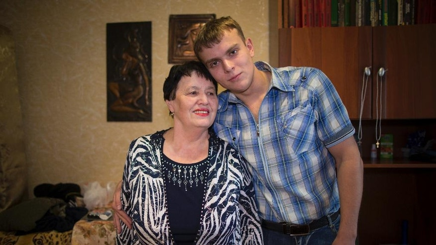 In this photo taken on Thursday, Oct. 27, 2016, Dmitry Batalov, 21, poses for a photo with his grandmother Lyubov Batalova, 67, at his family's apartment in Degtyarsk, Yekaterinburg region, Russia. Increasingly, the young men of Russia say they see military service as an opportunity, not a dreaded obligation to avoid. Batalov just earned a university degree in finance and law, looked at the civilian jobs on offer and concluded that a military life would be far more exciting. (AP Photo/Alexander Zemlianichenko)