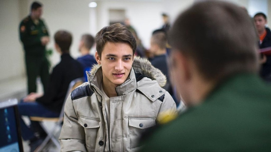 In this photo taken on Friday, Oct. 28, 2016, Vladislav Volkhin, left, talks to a serviceman at the military's recruitment center in Yekaterinburg, Russia. The 22-year-old graduate in information technology says he's joining the military because it offers better job prospects in a depressed economy. Volkshin hopes to learn plenty about high-tech computers and communications systems in uniform. (AP Photo/Alexander Zemlianichenko)
