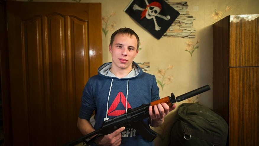 In this photo taken on Saturday, Oct. 29, 2016, Mikhail Galaktionov, 17, holds an airsoft rifle posing for a photo at his home in Pervouralsk, Yekaterinburg region, Russia. Increasingly, the young men of Russia say they see military service as an opportunity, not a dreaded obligation to avoid . Galaktionov says he hopes to hone his mechanic skills in Russia's tank corps. Those like him who don't progress from high school to university cannot proactively enlist and instead first serve one year as a poorly paid conscript earning just 2,000 rubles ($31) a month. (AP Photo/Alexander Zemlianichenko)