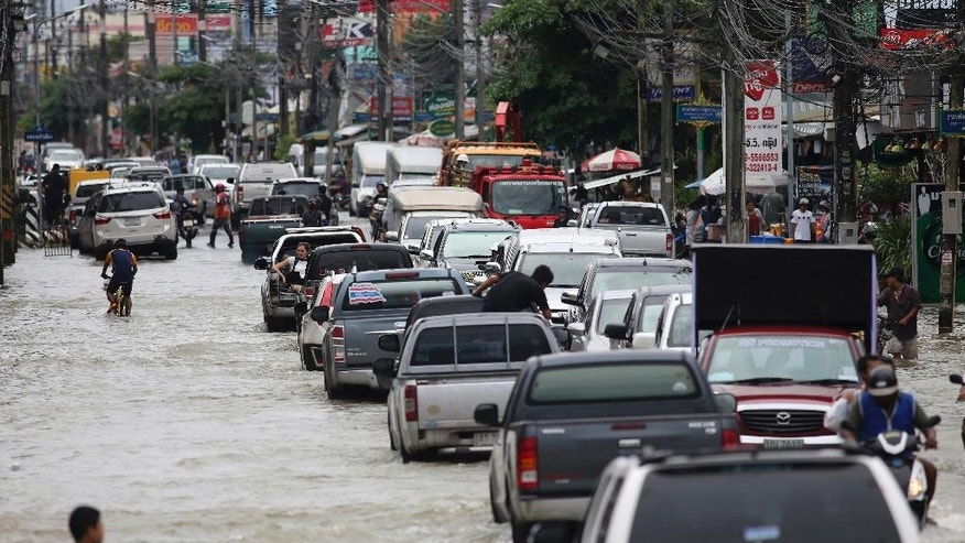 Residents drive through the flooded streets in the Nakon Si Thammarat province, southern Thailand, Tuesday, Dec. 6, 2016. Severe flooding due to heavy rain in the south over the past six days has killed more than a dozen people and affected 582,345 people in 11 of Thailand's 76 provinces the interior ministry said Tuesday. (AP Photo)