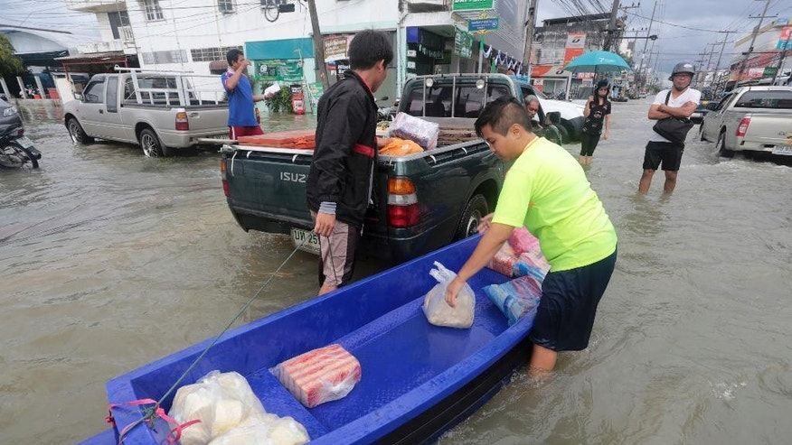 Residents use a canoe to ferry goods through the flooded streets in Nakon Si Thammarat province, southern Thailand, Tuesday, Dec. 6, 2016. Severe flooding due to heavy rain in the south over the past six days has killed more than a dozen people and affected 582,345 people in 11 of Thailand's 76 provinces the interior ministry said Tuesday. (AP Photo)