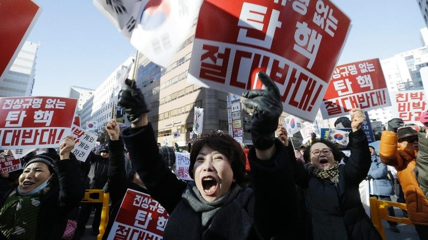 "Protesters supporting South Korean President Park Geun-hye shout slogans during a rally opposing the impeachment of South Korean President Park Geun-hye in front of the ruling Saenuri Party headquarters in Seoul, South Korea, Tuesday, Dec. 6, 2016. South Korea is entering potentially one of the most momentous weeks in its recent political history, with impeachment looming for Park as ruling party dissenters align with the opposition in a strengthening effort to force her out. The letters read ""Oppose the impeachment. "" (AP Photo/Ahn Young-joon)"