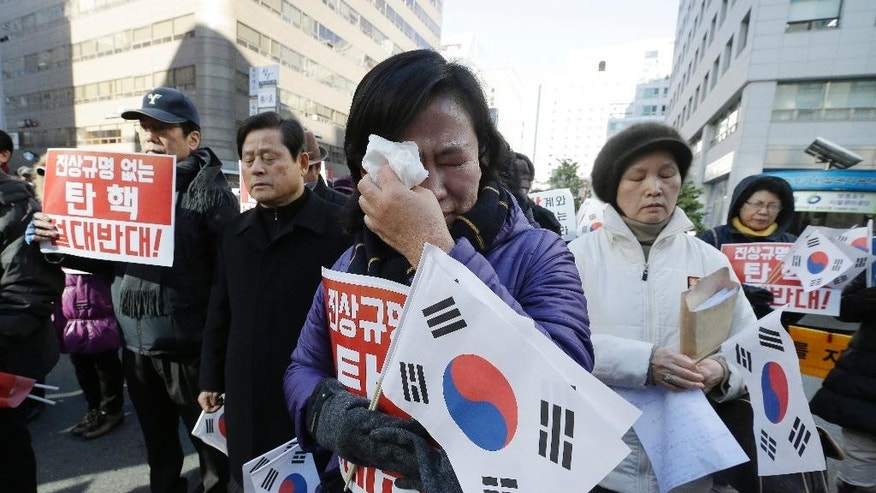 "A protester supporting South Korean President Park Geun-hye weeps as she listens to the national anthem during a rally opposing the impeachment of South Korean President Park Geun-hye in front of the ruling Saenuri Party headquarters in Seoul, South Korea, Tuesday, Dec. 6, 2016. South Korea is entering potentially one of the most momentous weeks in its recent political history, with impeachment looming for Park as ruling party dissenters align with the opposition in a strengthening effort to force her out. The letters read ""Oppose the impeachment. "" (AP Photo/Ahn Young-joon)"