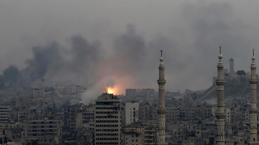 A ball of fire rises following a Syrian government air strike that hit rebel positions in the eastern neighborhoods of Aleppo, Syria, Monday, Dec. 5, 2016. The government seized large swaths of the Aleppo enclave under rebel control since 2012 in the offensive that began last week. The fighting was most intense Monday near the dividing line between east and west Aleppo as government and allied troops push their way from the eastern flank, reaching within less than a kilometer, about half a mile, from the citadel that anchors the center of the city. (AP Photo/Hassan Ammar)