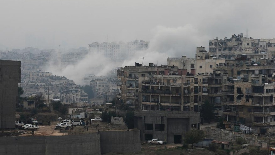 Smoke rises after rebel fighters launch a mortar shell on a residential neighborhood in western Aleppo, Syria, Monday, Dec. 5, 2016. The government seized large swaths of the Aleppo enclave under rebel control since 2012 in the offensive that began last week. The fighting was most intense Monday near the dividing line between east and west Aleppo as government and allied troops push their way from the eastern flank, reaching within less than a kilometer, about half a mile, from the citadel that anchors the center of the city. (AP Photo/Hassan Ammar)