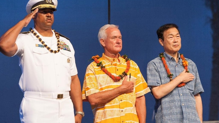 FILE - In this Aug. 15, 2015 file photo, U.S. Navy Read Adm. John Fuller, left, Honolulu mayor Kirk Caldwell, center, and then Nagaoka CityMayor Tomio Mori look on during a celebration marking the 70th anniversary of the end of World War II at Joint Base Pearl Harbor-Hickam, in Honolulu. The mayor of Nagaoka, Japan, the birthplace of the man who engineered the Pearl Harbor attack, is joining his counterpart of Honolulu to commemorate the 75th anniversary of the beginning of the four-year war between the two countries, as friends. Mayor Tatsunobu Isoda and eight other members of his delegation are formally invited as guests of Honolulu at both the main memorial on Wednesday, Dec. 7, 2016,  and a separate first ceremony Thursday, Dec. 8, co-organized by Japan and the U.S. (AP Photo/Marco Garcia, File)