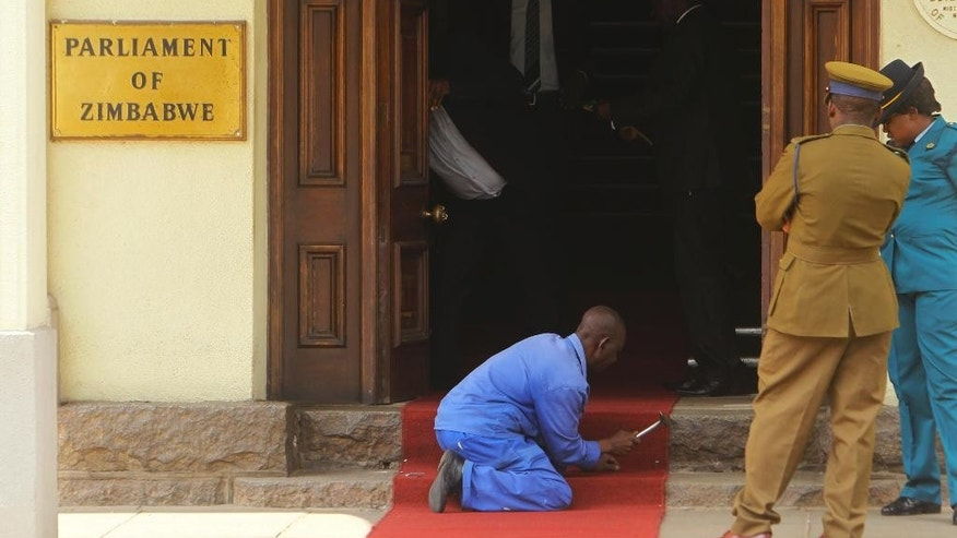 A worker ensures the red carpet is placed correctly before Zimbabwean President Robert Mugabe arrives for his annual State of the Nation address at Parliament in Harare, Tuesday, Dec. 6, 2016. Mugabe has appealed for calm, as his government battles to contain a debilitating economic crisis. (AP Photo/Tsvangirayi Mukwazhi)