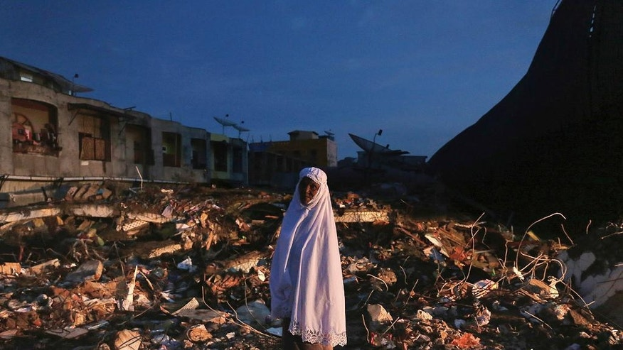 A woman stands on the ruin of a market after Wednesday's earthquake in Meureudu, Aceh province, Indonesia, early Thursday, Dec. 8, 2016. Thousands of people in the Indonesian province of Aceh took refuge for the night in mosques and temporary shelters after a strong earthquake Wednesday killed a large number of people and destroyed dozens of buildings. (AP Photo/Heri Juanda)
