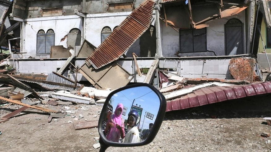 Women are reflected in a motorbike's mirror as they access the damaged building after an earthquake in Pidie Jaya, Aceh province, Indonesia, Wednesday, Dec. 7, 2016. A strong undersea earthquake rocked Indonesia's Aceh province early on Wednesday, killing a number of people and causing dozens of buildings to collapse. (AP Photo/Heri Juanda)