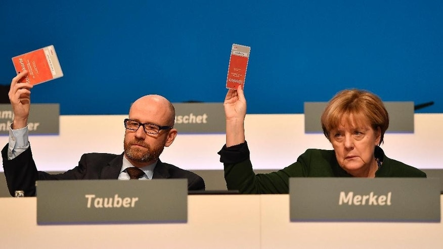 German chancellor Angela Merkel, right, and party secretary Peter Tauber vote at the general party conference of the Christian Democratic Union, CDU, in Essen, Germany, Wednesday, Dec. 7, 2016. Merkel has won a new term as the leader of Germany's main conservative party after stressing her determination to prevent a repeat of last year's huge migrant influx and advocating a partial ban on face-covering veils. (AP Photo/Martin Meissner)