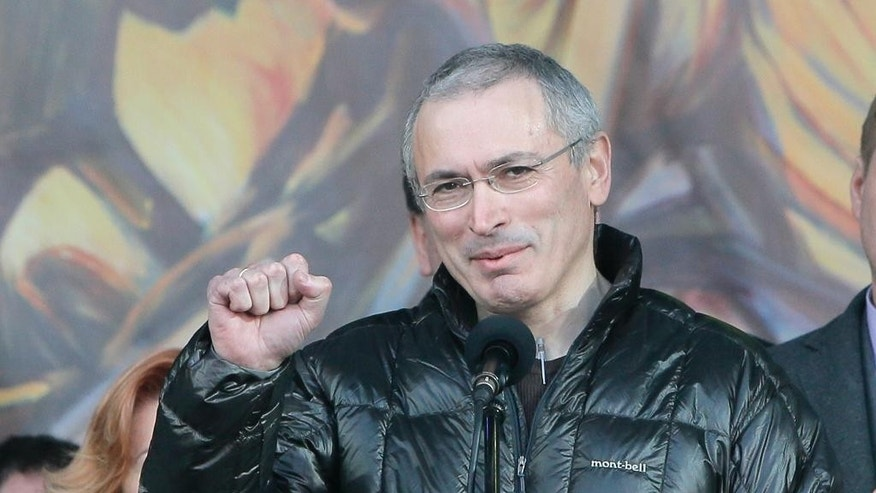 FILE - In this March 9, 2014 file photo, Russian former oil tycoon Mikhail Khodorkovsky cheers people during a rally in Independence Square in Kiev, Ukraine. A Dublin judge ordered authorities on Wednesday, Dec. 7, 2016, to unfreeze 100 million euros ($107 million) in cash belonging to Khodorkovsky, ruling that police had provided no evidence that the funds were illegally gained as Russia contends. (AP Photo/Efrem Lukatsky, File)