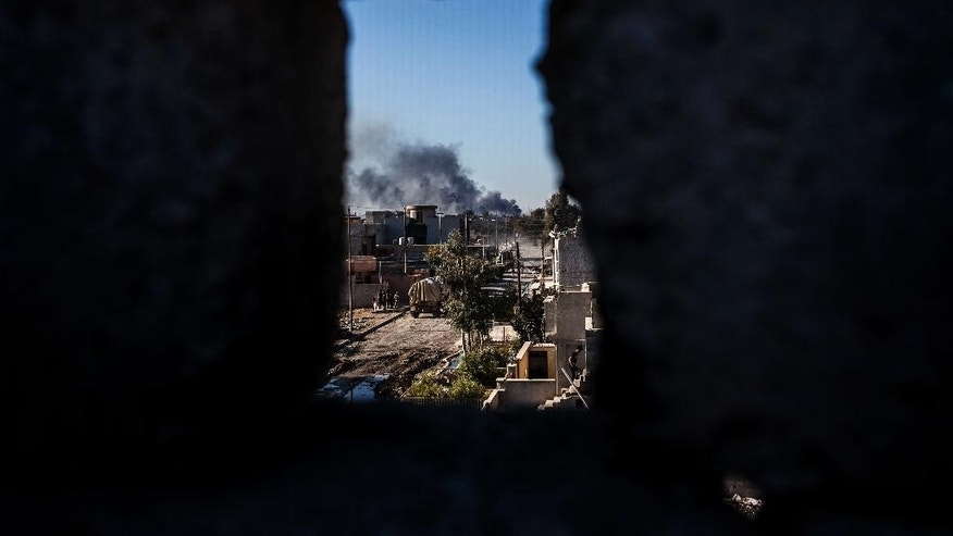 Smoke rises at the frontline, seen from an Iraqi army shooting position in Shyma district in Mosul, Iraq, Tuesday, Dec. 6, 2016. Iraqi forces, backed by the U.S.-led international coalition, launched a campaign in October to retake Mosul, the country's second largest city and IS's last major urban bastion in Iraq. (AP Photo/Manu Brabo)