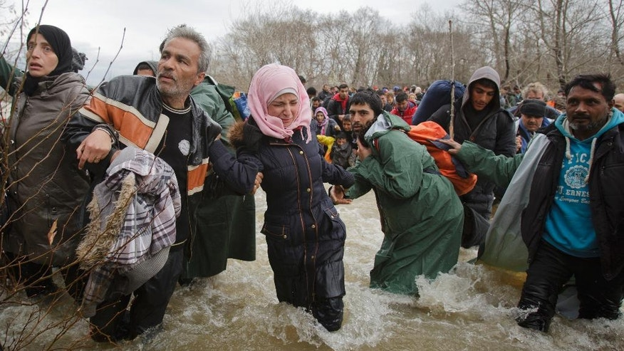 2016 AP YEAR END PHOTOS - A woman cries as she crosses the river along with other migrants, north of Idomeni, Greece, attempting to reach Macedonia on a route that would bypass the border fence, on March 14, 2016. (AP Photo/Vadim Ghirda, File)