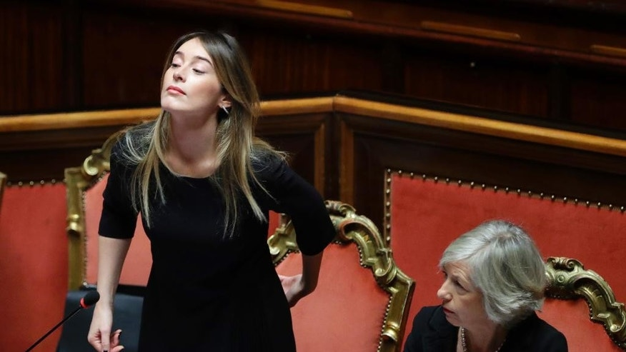 Italian Minister of Constitutional Reforms and Relations with Parliament, Maria Elena Boschi, left, flanked by Education Minister Stefania Giannini attend a session of the Senate in Rome, Wednesday, Dec. 7, 2016. Calls have mounted rapidly from populist and other opposition leaders for quick elections in Italy, seeking to capitalize on Premier Matteo Renzi's humiliating defeat in a referendum on government-championed reforms. The president, though, told Renzi to stay in office a bit longer until a critical budget law is passed. (AP Photo/Alessandra Tarantino)