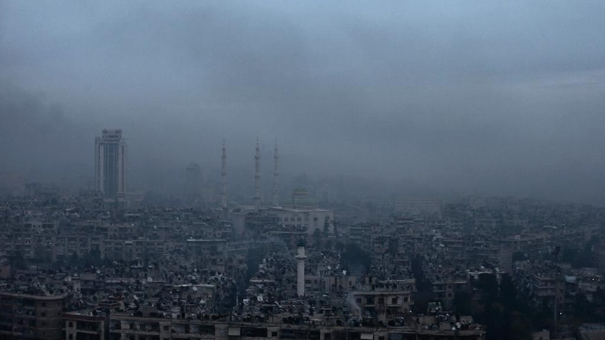 In this picture taken Monday, Dec. 5, 2016, smoke rises in a east Aleppo neighborhood during a battle between forces loyal to Syrian President Bashar Assad and rebels in Aleppo, Syria. A Syrian war monitoring group says government forces have captured large parts of Aleppo's central-eastern al-Shaar neighborhood from rebels. The Britain-based Syrian Observatory for Human Rights says government forces took most of the once-populous neighborhood Tuesday following intense clashes. (AP Photo/Hassan Ammar)