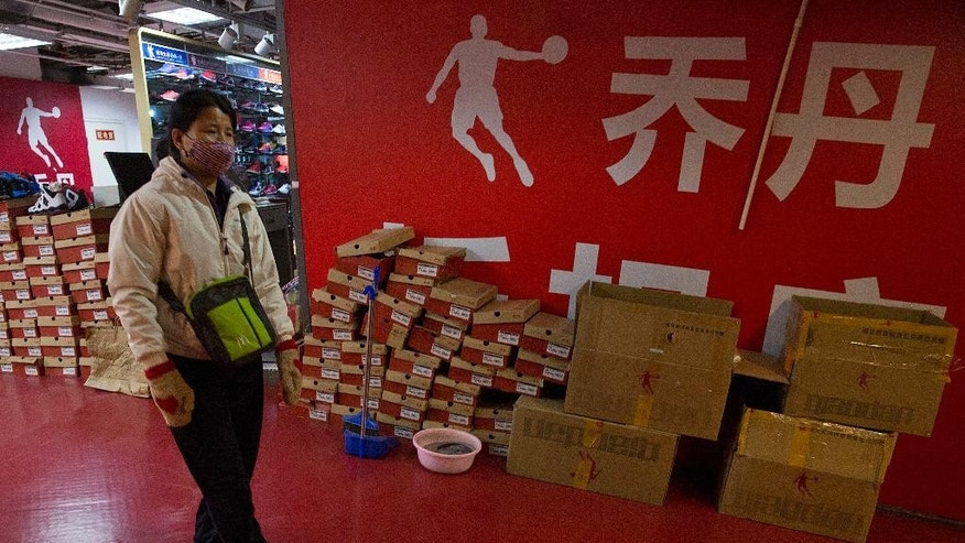 A shopper walks past a Qiaodan Sports retail shop in Beijing, China, Thursday, Dec. 8, 2016. China's highest court on Thursday ruled in favor of basketball legend Michael Jordan at the culmination of a years-long case over use of the Chinese rendering by Qiaodan Sports of his globally-known name and trademark. (AP Photo/Ng Han Guan)