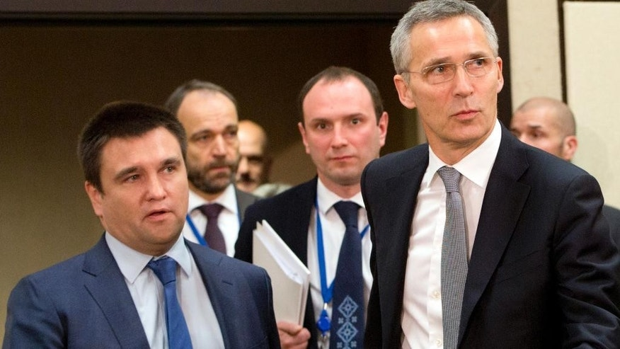 NATO Secretary General Jens Stoltenberg, second right, and Ukrainian Foreign Minister Pavlo Klimkin, left, arrive for a round table meeting of the NATO-Ukraine Commission at foreign ministers level at NATO headquarters in Brussels on Wednesday, Dec. 7, 2016. (AP Photo/Virginia Mayo)