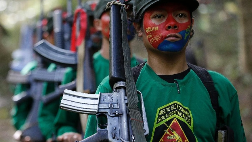 FILE -  this file photo taken Nov. 23, 2016, members of the New People's Army communist rebels march with firearms at their guerrilla encampment tucked in the Sierra Madre mountains southeast of Manila, Philippines. Philippine communist rebels warned President Rodrigo Duterte Wednesday that they may be forced to end their monthslong cease-fire and resume fighting if he does not suspend the government's counterinsurgency program and withdraw troops from rebel-influenced areas. (AP Photo/Aaron Favila, File)