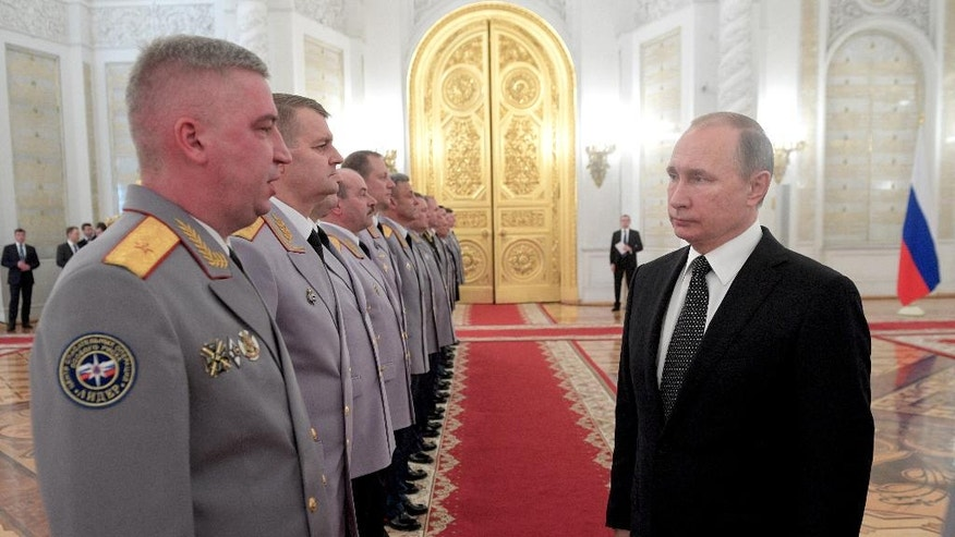 Russian president Vladimir, right, congratulates newly appointed senior military staff in the Kremlin, in Moscow, Russia, Wednesday, Dec. 7, 2016. Putin on Wednesday paid respects to Russian medics and a colonel who died while on duty in Syria. (Alexei Druzhinin/Sputnik, Kremlin Pool Photo via AP)