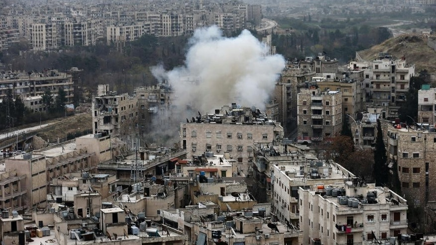 Smoke rises after rebel fighters launch a mortar shell on residential neighborhood in west Aleppo, Syria, Monday, Dec. 5, 2016. The government seized large swaths of the Aleppo enclave under rebel control since 2012 in the offensive that began last week. The fighting was most intense Monday near the dividing line between east and west Aleppo as government and allied troops push their way from the eastern flank, reaching within less than a kilometer (half a mile) from the citadel that anchors the center of the city.(AP Photo/Hassan Ammar)
