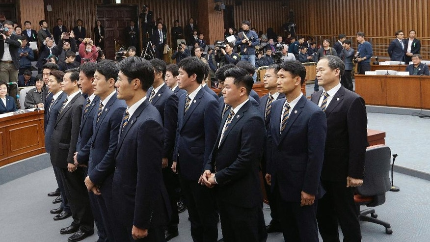 Parliamentary security officers stand during a hearing at the National Assembly in Seoul, South Korea, Wednesday, Dec. 7, 2016. A South Korean parliamentary committee on Wednesday ordered Choi Soon-sil, the jailed woman at the center of a scandal, that threatens to bring down President Park Geun-hye to attend a hearing investigating her alleged manipulation of government affairs. (AP Photo/Ahn Young-joon, Pool)
