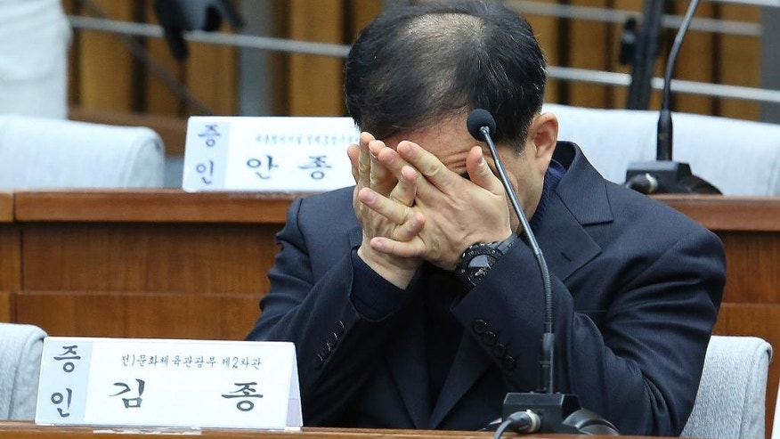Former South Korean Vice Sports Minister Kim Chong covers his face with hands during a hearing at the National Assembly in Seoul, South Korea, Wednesday, Dec. 7, 2016. A South Korean parliamentary committee on Wednesday ordered Choi Soon-sil, the jailed woman at the center of a scandal, that threatens to bring down President Park Geun-hye to attend a hearing investigating her alleged manipulation of government affairs. (AP Photo/Ahn Young-joon, Pool)