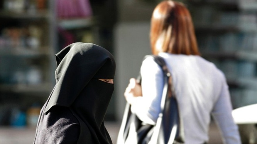 A Muslim woman walks down the street in Blackburn, England.
