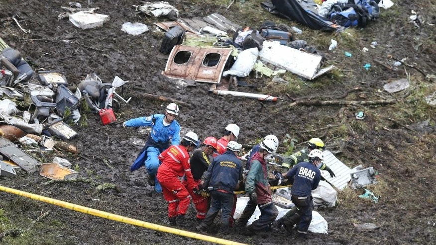 FILE -  In this Nov. 29, 2016, file photo, rescue workers recover a body from the wreckage site of an airplane crash, in La Union, a mountainous area near Medellin, Colombia. The chartered plane was carrying a Brazilian soccer team to the biggest match of its history when it crashed into a Colombian hillside and broke into pieces. The Bolivian aviation official who signed off the flight plan of the chartered aircraft is breaking her silence in a public letter published on Thursday, Dec. 8, accusing her bosses of trying to stage a cover-up. (AP Photo/Fernando Vergara, File)
