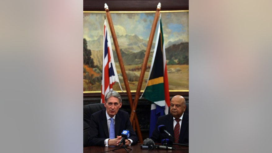 Britain's finance chief, Philip Hammond, left, speaks whilst South Africa's Finance Minister, Pravin Gordhan, watches during their media briefing in Pretoria, South Africa, Wednesday, Dec. 7, 2016. Hammond is in South Africa to try to reassure global partners ahead of his country's planned departure from the European Union. (AP Photo/Themba Hadebe)