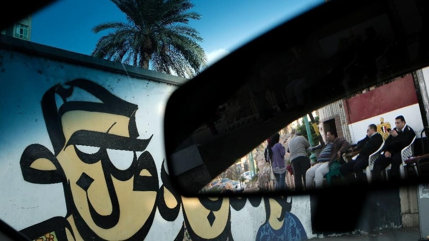 "FILE -- In this Wednesday, Dec. 7, 2016 file photo, Egyptian policemen are reflected in a car mirror as they sit near graffiti displayed on a wall in Cairo, Egypt. On Thursday, Dec. 8, 2016, Egypt's president defended the tough economic measures his government has undertaken, at a gathering of clerics ahead of the Prophet's Birthday, a major Islamic holiday, saying there was no alternative in the face of deteriorating economy. In his speech, the army-chief-turned-president also reiterated earlier warnings against any attempts to ""topple the state."" (AP Photo/Nariman El-Mofty, File)"