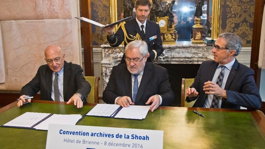 Radu Ioanid, director of the International Archival Programs Division at the United States Holocaust Memorial Museum, left, French Secretary of State for Veterans and Remembrance Jean-Marc Todeschini, center, and Jacques Fredj, Executive Director of France's Shoah Memorial attend a signing ceremony in Paris, Thursday, Dec. 8, 2016. France's Defense Ministry signs a deal to hand over digitized versions of its archives around World War II persecution of Jews to Holocaust museums in Washington and Paris so that the public can access them. (AP Photo/Michel Euler)