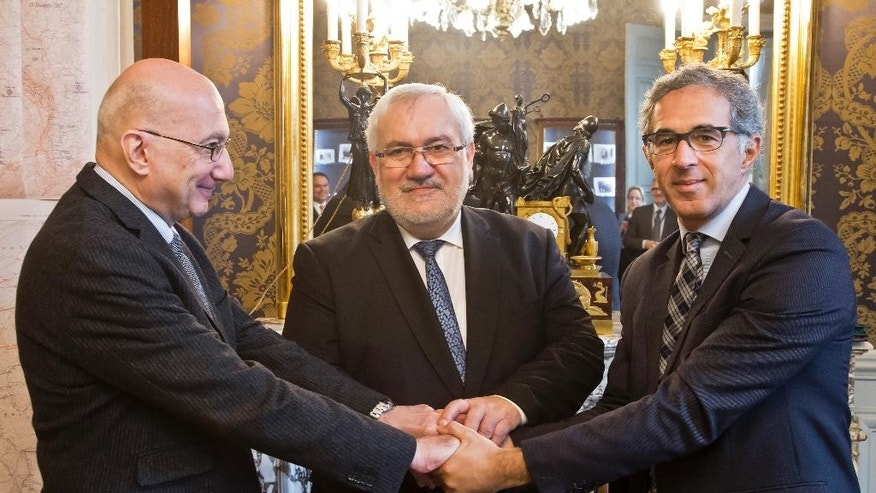 Radu Ioanid, Director of the International Archival Programs Division at the United States Holocaust Memorial Museum, left, French Secretary of State for Veterans and Remembrance Jean-Marc Todeschini, center, and Jacques Fredj Executive Director of France's Shoah Memorial shake hands after a signing ceremony in Paris, Thursday, Dec. 8, 2016. France's Defense Ministry signs a deal to hand over digitized versions of its archives around World War II persecution of Jews to Holocaust museums in Washington and Paris so that the public can access them. (AP Photo/Michel Euler)