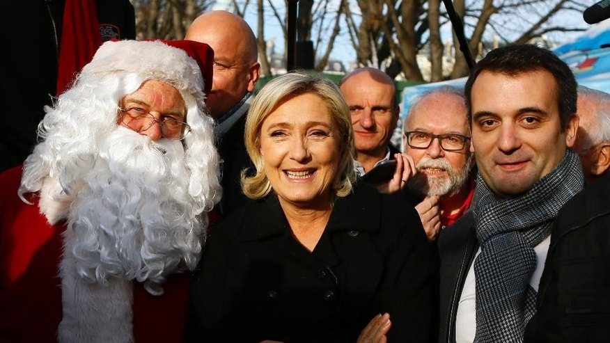 Dec. 8, 2016: Far-right leader and candidate for next spring's presidential elections Marine le Pen, center flanked with French far-right Front National vice-president Florian Philippot, right, and lawyer Wallerand de Saint Just, second right, pose with a Santa Claus during a visit at Champs Elysees Christmas market in Paris.